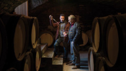 Men tasting wine in barrel room