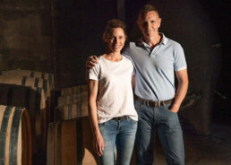 Emma and Rod standing next to wine barrels