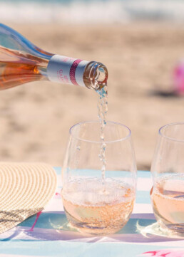 Rose being poured into glass at the beach