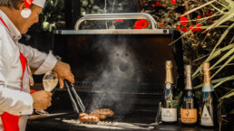 Sausage sizzle with champagne bottles sitting on top of BBQ