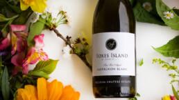 Bottle of wine lying among flowers