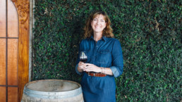 Woman standing next to wine barrel drinking wine